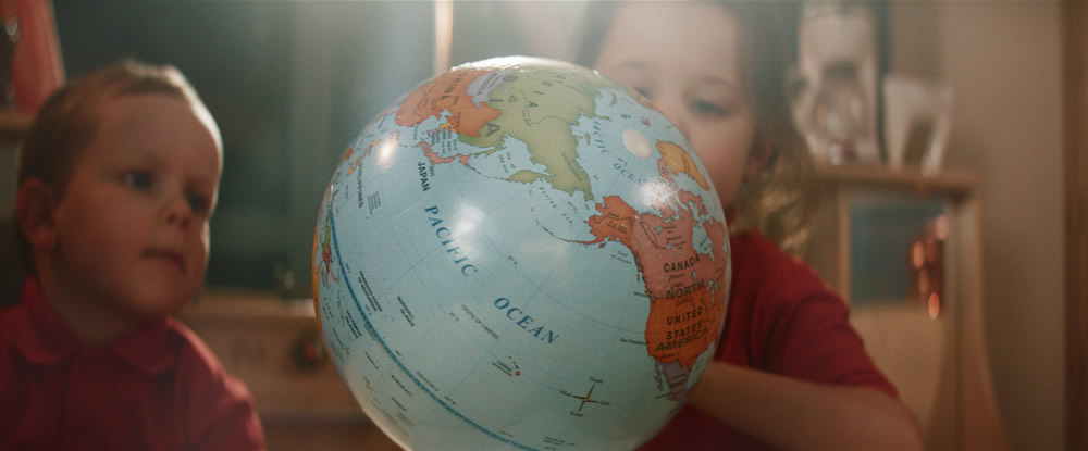 Children looking at a globe and the pacific region