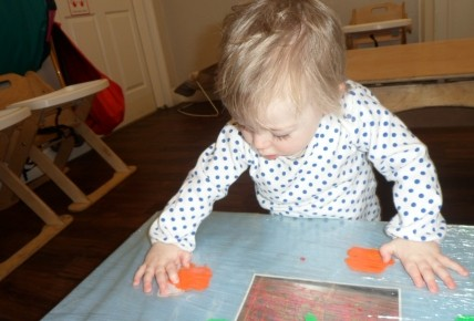 Etta creating different patterns with the paint.