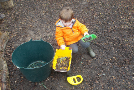 Toddlers collecting natural materials in the garden to extend their role play.