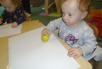 Babies using different colour's to draw shapes